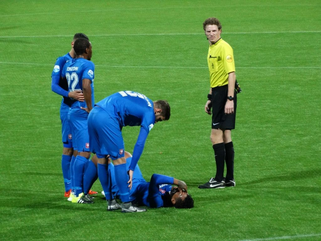 Arbiter Van de Kerkhof kijkt toe bij de blessurebehandeling van Tapia.